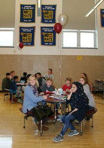 picture of students and teacher seated around lunch table talking