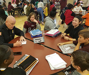 picture of students and police chief seated around lunch table talking