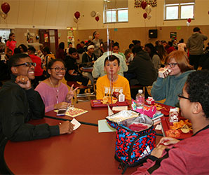 picture of student leaders and grades 7-8 students seated around lunch table talking