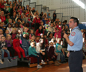 picture of firefighter talking to large group of students seated on bleachers in gym